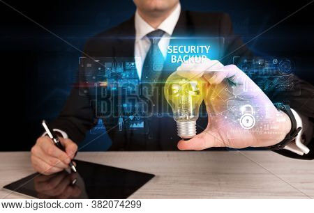 Businessman holding lightbulb with SECURITY BACKUP inscription, online security idea concept
