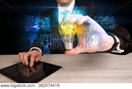 Businessman holding lightbulb with RELIABLE PROTECTION inscription, online security idea concept