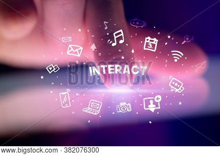 Finger touching tablet with drawn social media icons and INTERACT inscription, social networking concept