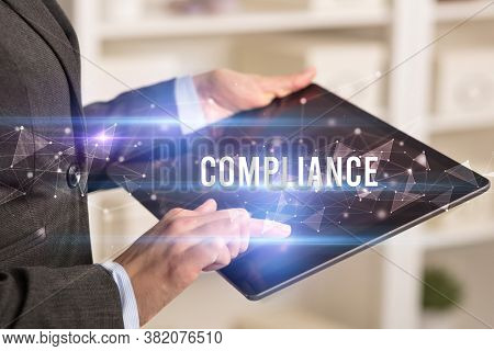 Close up hands using tablet with COMPLIANCE inscription, modern business technology concept