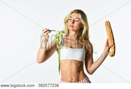 Calories Carbs And Gluten. Healthy Eating. Athletic Woman In Sportswear With Measuring Tape On Fork.