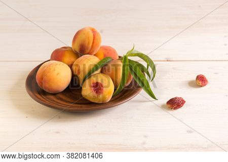Many Ripe Velvety Juicy And Beautiful Peaches With Leaves Lie In A Plate On A White Wooden Table. Su