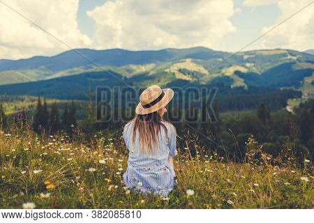 Traveling In Summer Ukraine. Trip To Carpathian Mountains. Woman Tourist Sitting In Flowers Admiring