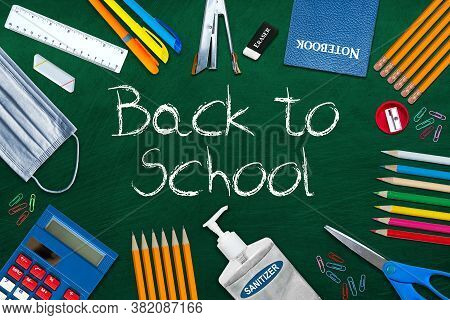 Back To School During Covid-19 Pandemic With Chalkboard Surrounded By Stationery. Education Concept