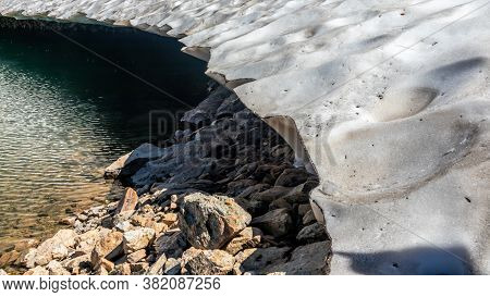 Glacial Lake Of Melting Ice Of Glacier And Rocks In Summer. Partially Frozen. Landscape Scene In Aos