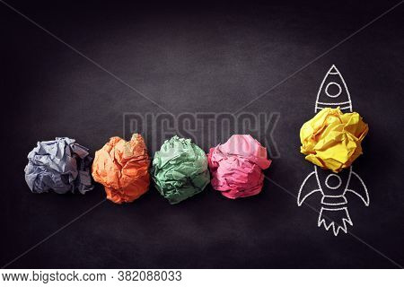 Rocket chalk drawing paper ball on blackboard blast off for successful business startup idea
