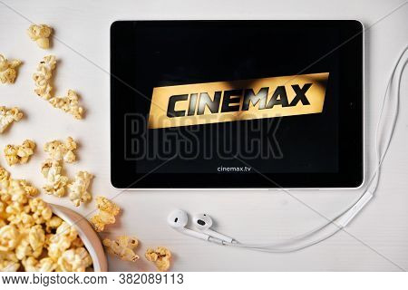 Cinemax On The Screen Of The Tablet With Popcorn Box And Apple Earphones On The Background. Advertis
