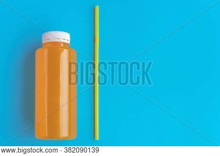 Non-alcoholic Orange Carbonated Drink In A Plastic Bottle With A Cocktail Tube On A Blue Background,