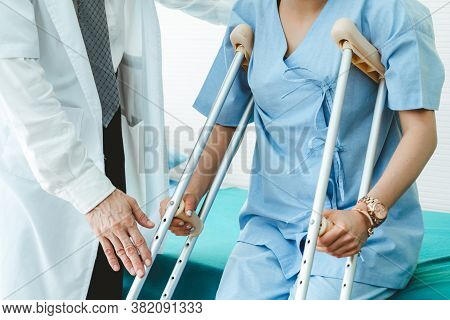 Doctor Takes Care Of Patient In Crutch At Hospital. Physical Therapist And Leg Injury Recovery Conce