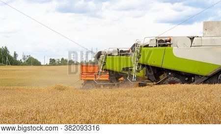 Backs Of Combines And Truck Trailer Lined Up In A Row In A Wheat Field Against A Blue Sky With Cloud