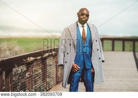 Portrait Of A Fashionable Bald Bearded Mature Black Guy In An Elegant Blue Costume With A Necktie, S
