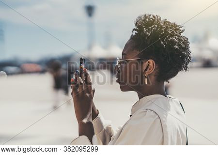 Side View Of A Cute Black Hipster Girl In Spectacles And White Trench Taking Pics Of The Camera Of H