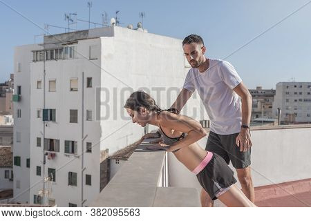 Young Female Athlete Doing Incline Push-ups On The Roof Of A Building, While Being Supervised By Her