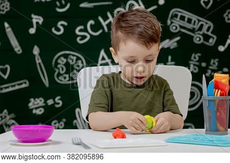 Cute Little Boy Moulds From Plasticine On Table With A Blackboard On A Background. Ready For School.
