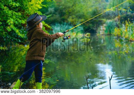 Little Boy Child Catching A Fish. Kid With Fishing Rod At Lake. Lonely Happy Little Boy Fishing From