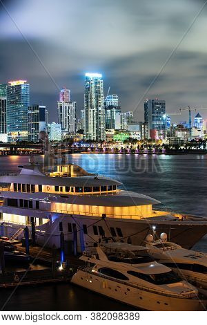 Miami Florida At Sunset, Skyline Of Illuminated Yacht Or Boat. Miami City Night