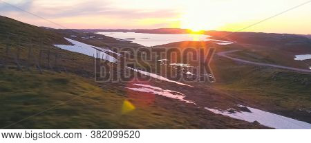 Sunset In The Tundra Among The Hills. Hilly Tundra.
