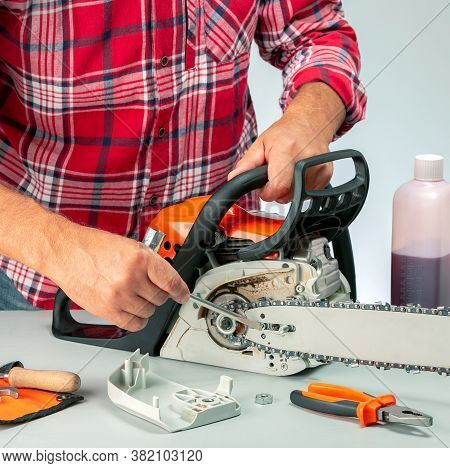 Man Repairing A Chainsaw In Workbench . Small Business.