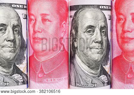 Close Up Rolls 100 Us Dollar And 100 Chinese Yuan Renminbi Banknotes Background.