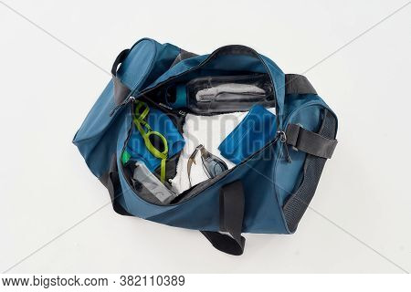 Swimming Equipment. Top View Of Sports Bag With Swim Goggles, Hat Or Cap, Towel And Bottle Of Water