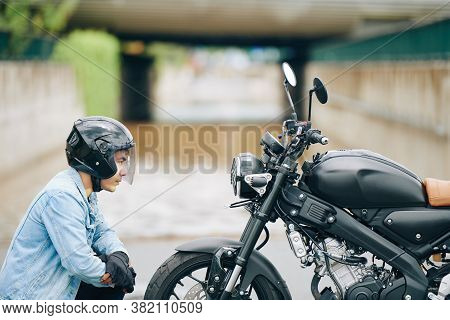 Serious Vietnamese Biker In Helmet Looking At Headlight Of Motorcycle