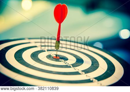 Red Dart Arrow Hitting In The Target Center Of Dartboard On Bullseye For Business Focus Concept.