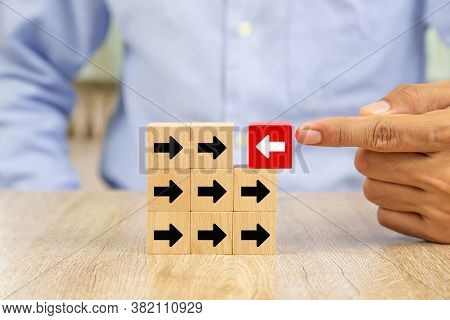 The Hand Selected The White Arrow Icon On The Wooden Block Which Has The Opposite Direction With The