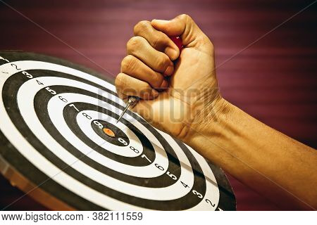 Arrow Hitting In The Target Center Of Bullseye,hand Holding The Arrow To Dartboard Center For Busine