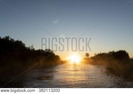 Sunrise Sky Background. Gold Sunrise Sky With Sky Clouds Over The Lake With Fog.crystal Clear Water