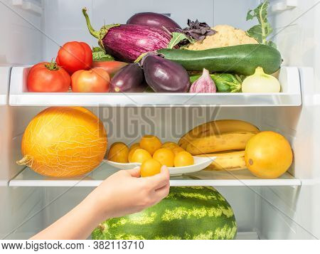 Woman's Hand Picks Up Plum From The Refrigerator Shelf. Hand Takes A Plum From The Refrigerator. The