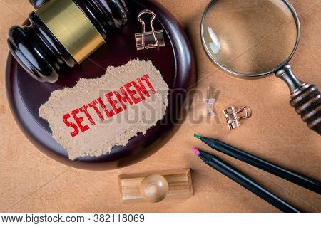 Settlement. Laws, Litigation, Lawyers And Compromise Concept. Wooden Court Hammer And Magnifying Gla