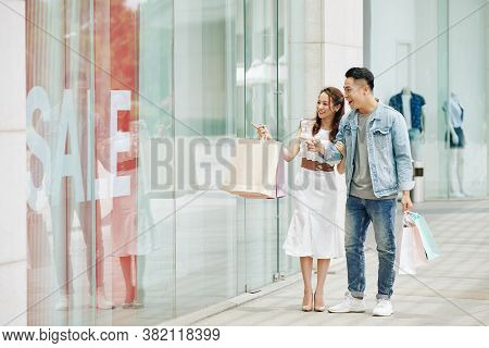 Young Vietnamese Couple Shopping In Mall On Weeked, Walking And Looking Through Shop Window