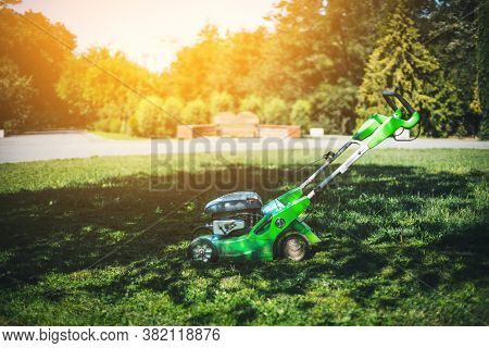 Professional Lawn Mower On The Grass. Cleaning And Caring For The Vegetable Garden, Garden And Park