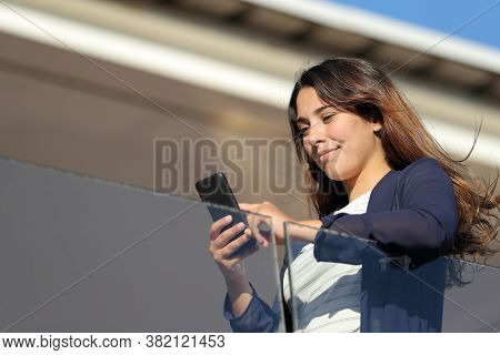 Apartment Renter Checking Smart Phone In A Balcony A Sunny Day