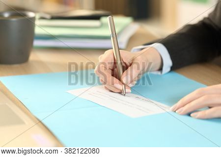 Close Up Of Entrepreneur Woman Hands Filling Bank Check Sitting On A Desk At Homeoffice