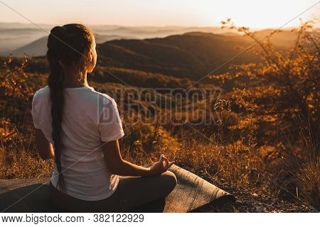 Woman Meditating Alone On Hill With Amazing Autumn Mountain View At Sunset. Zen Spiritual Concept. P