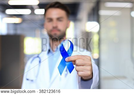 Doctor Hand With Blue Prostate Cancer Awareness Ribbon. Medicine Oncology Closeup Sky Symbol.
