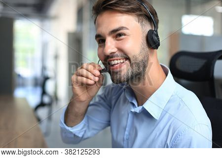 Cheerful Young Support Phone Male Operator In Headset, At Workplace While Using Laptop, Help Service