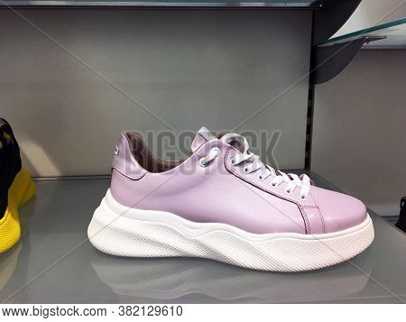 White Platform Sneakers With Bright Color Accents On Shelf In Shoes Store. Mass Market Shop. Close V