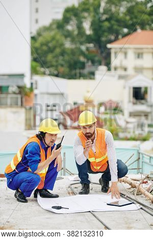 Head Engineer Checking Construction Plan When Contractor Controlling Work Of Builders Via Walkie-tal