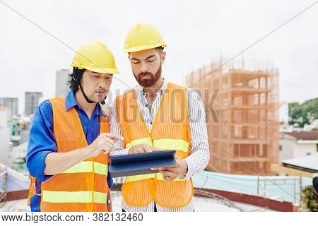 Serious Multi-ethnic Contractor And Builder Discussing Blueprint Or Work Schedule On Tablet Computer