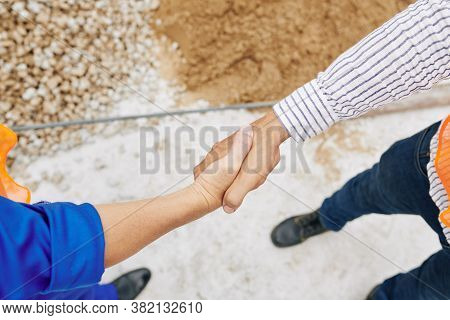 Contractor Shanking Hand Of Builder To Thank Him For Good Work, View From Above