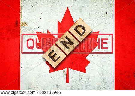 End Of Quarantine. The Inscription On Wooden Blocks On The Background Of The Flag Of Canada. The End
