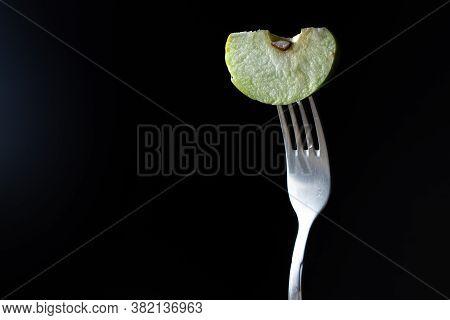 A slice of apple on a fork on a black background. Sliced green apple slice