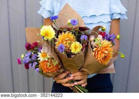 Woman In Blue Blouse Holding Beautiful Bouquets Of Flowers. Hands With Bouquets Of Seasonal Flowers