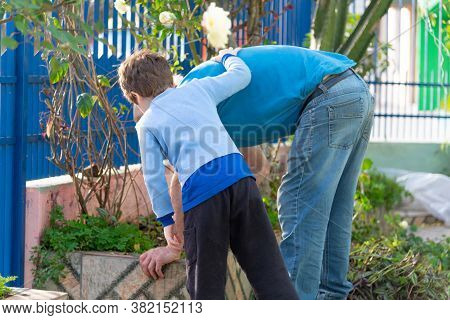 Grandfather And Grandson Cleaning The House Garden