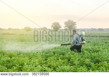 Farmer With A Mist Sprayer Blower Processes The Potato Plantation. Protection And Care. Environmenta