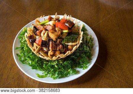 Stir-fried Chicken With Cashew Nuts Recipe In Basket Of Fried Taro. Thai-style Stir-fried Chicken Wi