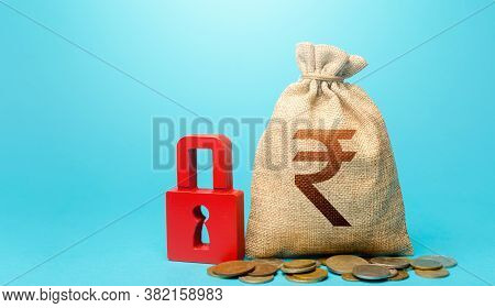 Indian Rupee Money Bag And Red Padlock. Blocking Bank Accounts And Seizing Assets. Freezing Of Pensi