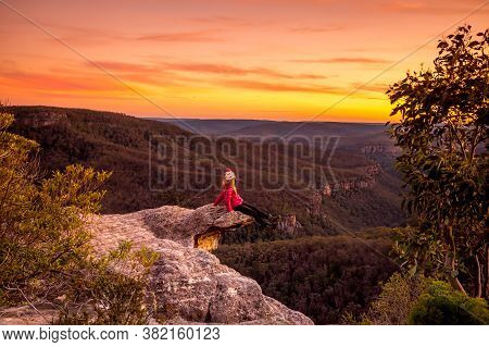 Hiker Takes A Rest, Sitting On Edge Of Rock Precipice With Escarpment And Valley Views And Vivid Sun